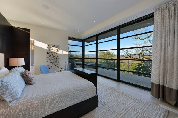 Master Bedroom highlights include wood flooring, fireplace, dual closets with built- in safe, retractable built-in television, and adjacent sitting room.  Glass walls open to the terrace and magnificent vantage points.